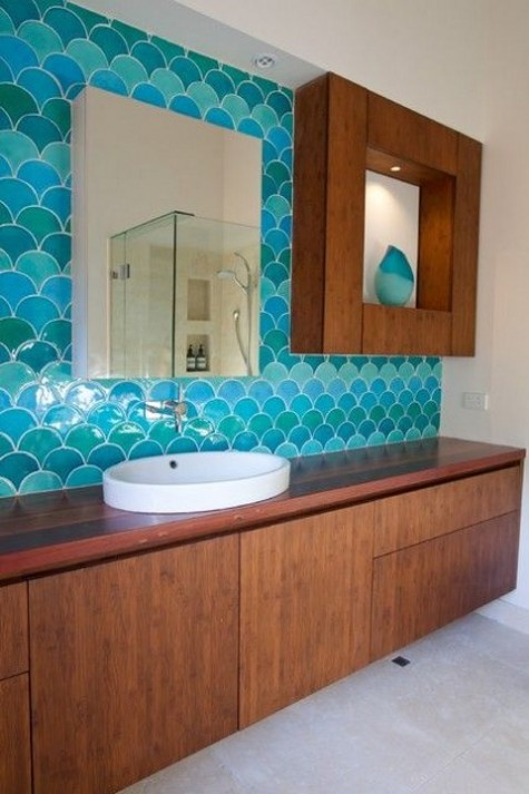 bold blue fishscale tiles cover one bathroom wall and make the rich stained furniture stand out a lot