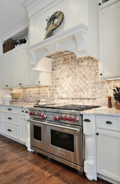 red brick was whitewashed here to make the look softer and match the white kitchen with stone countertops