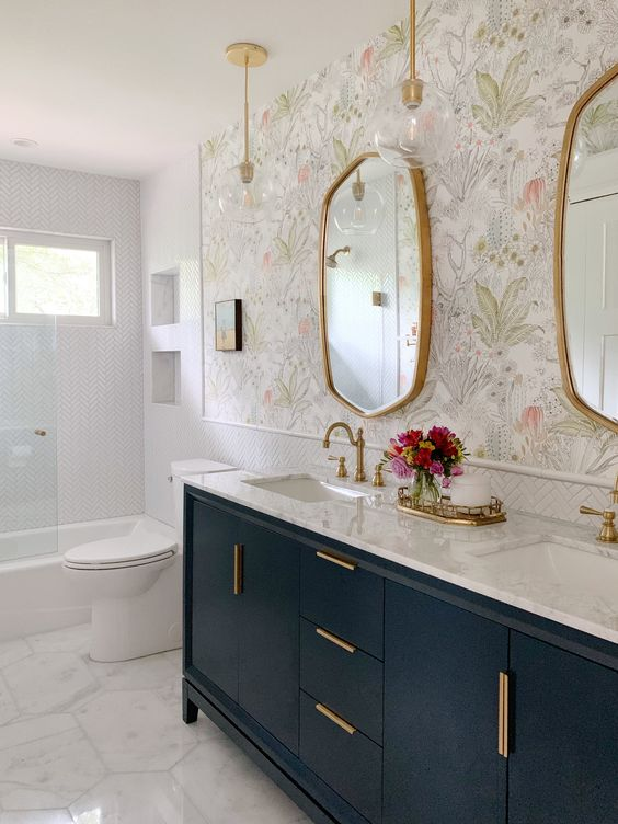 a beautiful bathroom with white tiles, floral wallpaper, a navy vanity and touches of gold for more chic