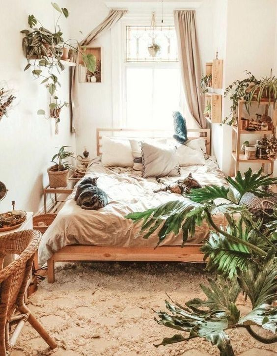 a small boho bedroom with a large bed, some wooden and wicker items and potted greenery