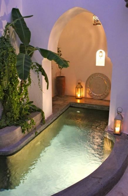 a small boho pool space with a pool with inner lights, candle lanterns, decor and potted plants