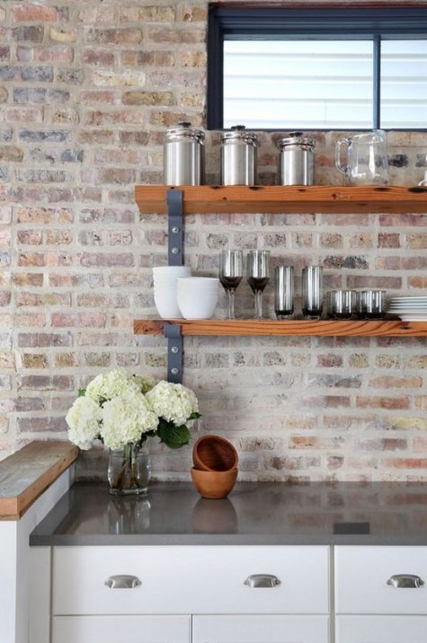 white cabinets, grey countertops and a whitewashed red brick backsplash that adds texture and eye-catchiness to the space