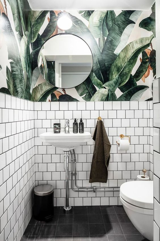 a chic powder room with tropical leaf wallpaper, white tiles and neutral metallics feels tropical