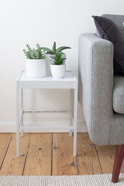 an IKEA Nesna hack done with contact paper and glass underneath makes up a cool side table