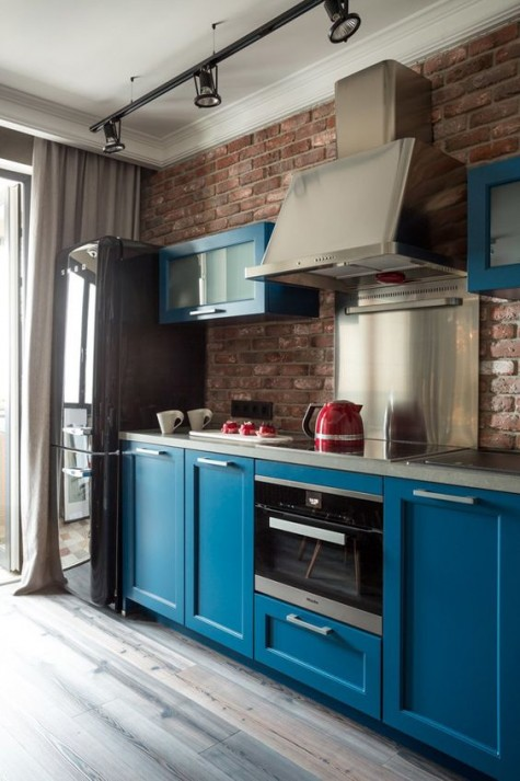a bold blue kitchen with dark touches and a red brick kitchen backsplash plus shiny metal touches