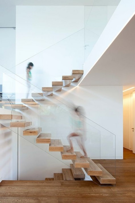 a floating staircase made of wood and with glass railing that holds the steps at the same time looks very modern