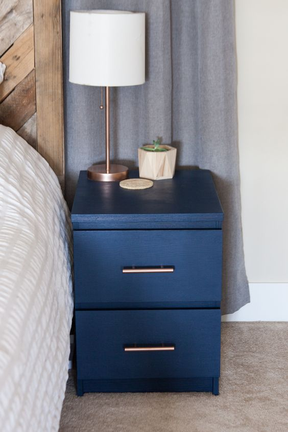 an IKEA Malm nightstand hacked with navy paint and chic brass handles looks very cool and bold
