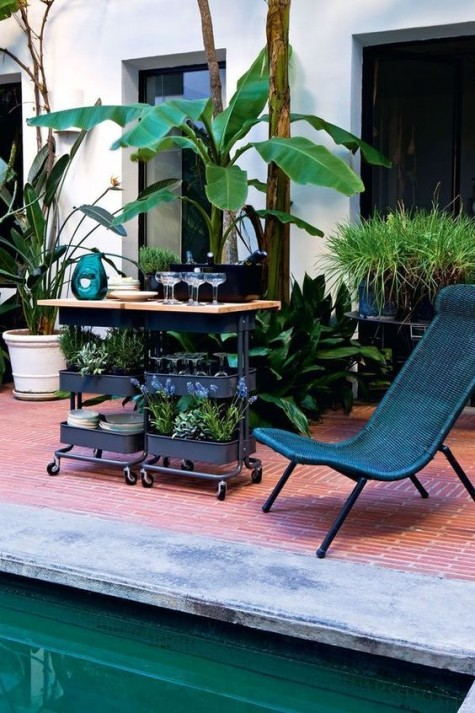 an outdoor bar in black with a wooden countertop using two IKEA Raskog carts for storage