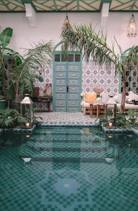 a beautiful Moroccan pool space with mosaic tiles, blue inlay doors, potted greenery, lanterns and rattan furniture