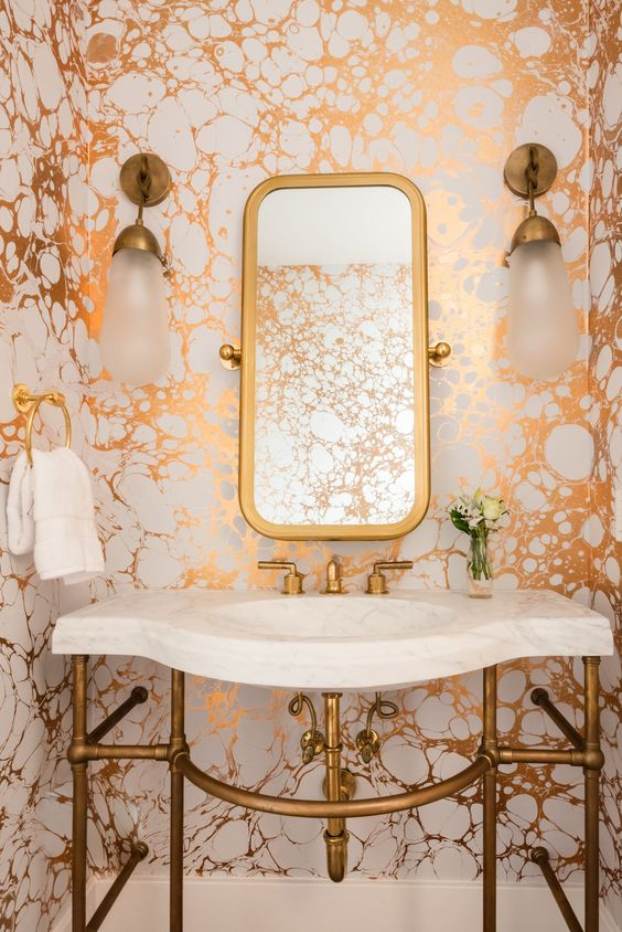 a bright powder room with metallic marble wallpaper, brass touches and a white stone sink