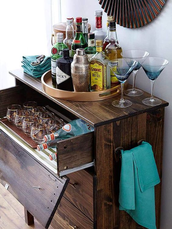 a dark stained IKEA Tarva dresser with a pullout drawer for stashing glasses and bottles is a rustic bar idea