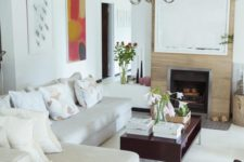 11 a small eclectic living room with a large sectional sofa, a fireplace, a coffee table and a chair, nothing else