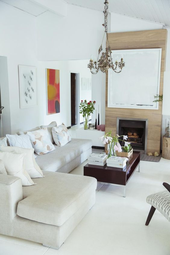 a small eclectic living room with a large sectional sofa, a fireplace, a coffee table and a chair, nothing else