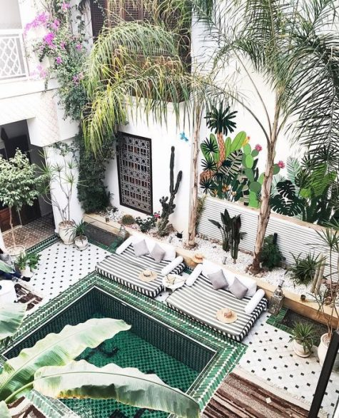 a bright Moroccan pool spacefully done with amazing tiles, a pool with steps, potted greenery and a daybed, rugs and an elegant console
