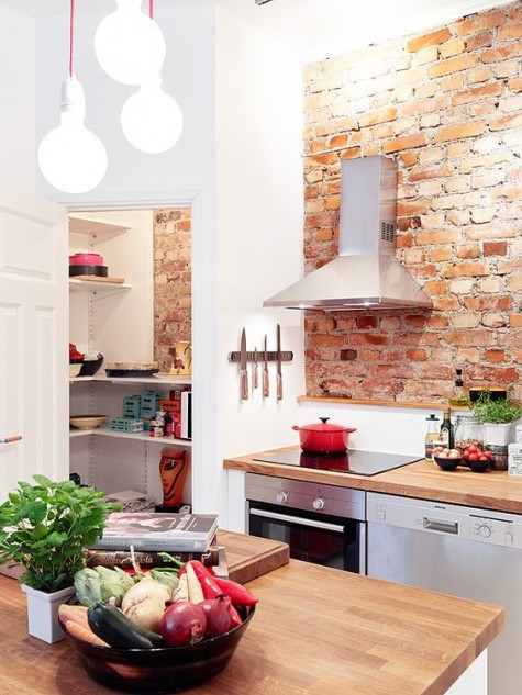 a chic Scandinavian kitchen with red touches and a red brick backsplash for a texture and bolder look