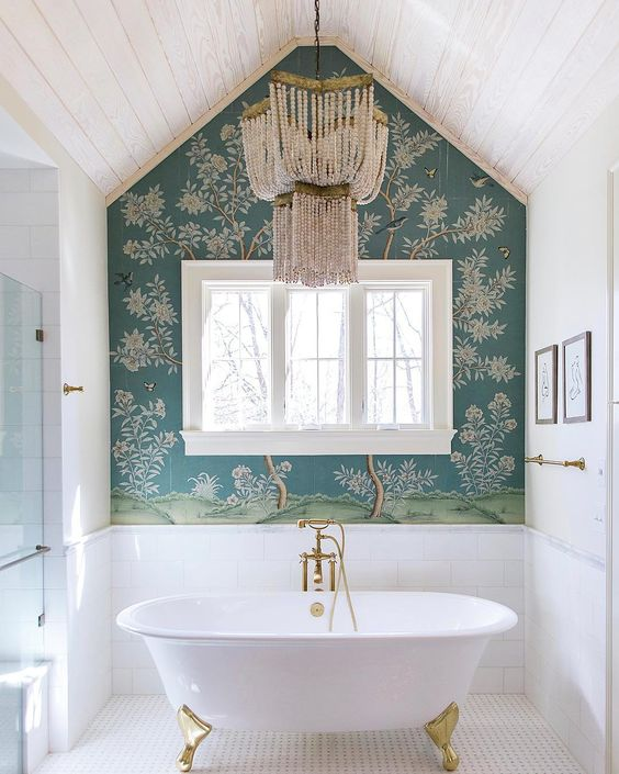 a refined bathroom with a navy botanical wallpaper wall, a vintage tub and crystal chandelier over it