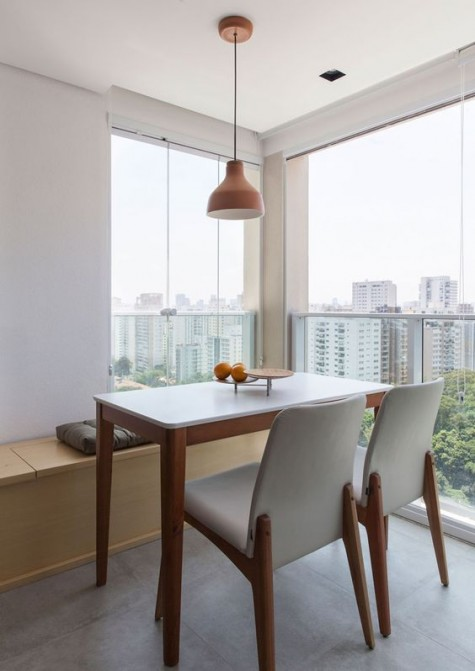 a small contemporary dining space done with a bench with storage space and a couple of chairs