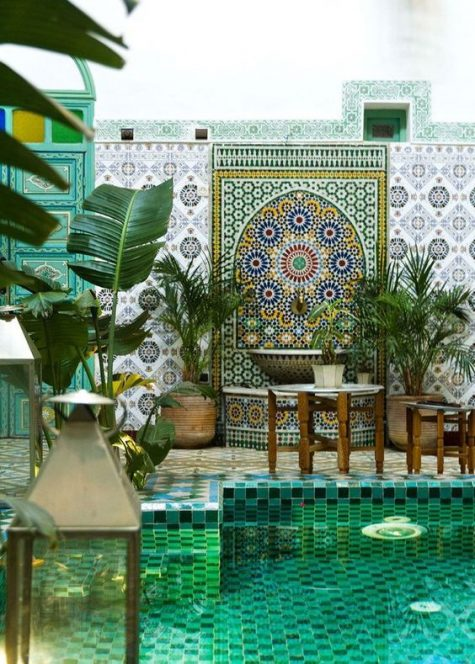 a colorful Moroccan pool space with several tiles of gorgeous tiles, potted greeneyr, vintage furniture and lanterns