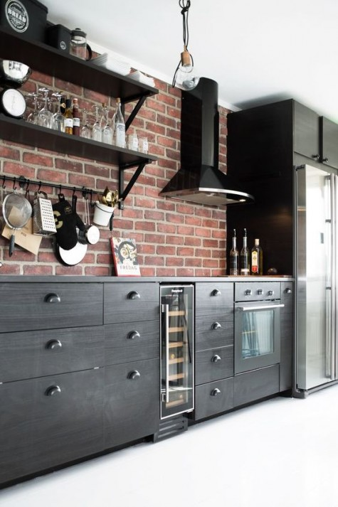 a dark masculine kitchen is spruced up with a red brick backsplash for more texture and shiny metal touches