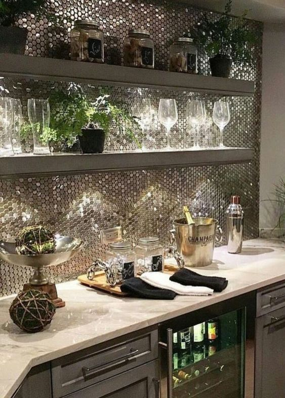 a refined home bar styled with shiny silver penny tiles to make the space stand out in an open layout