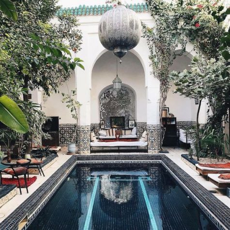 a gorgeous Moroccan pool space with hanging lanterns, bright furniture, loungers, mosaic tiles and pillars