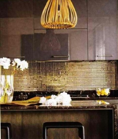 a shiny gold tile backsplash adds a luxurious feel to the kitchen and the combo of chocolate brown and gold is bold