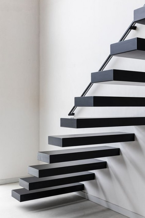 blackened metal floating stairs will perfectly fit a minimalist space and make a statement with color