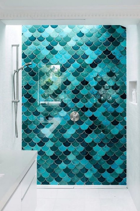 sea-inspired misatching in color but matching in size fishscale tiles accentuate the shower space and make it stand out in the neutral space