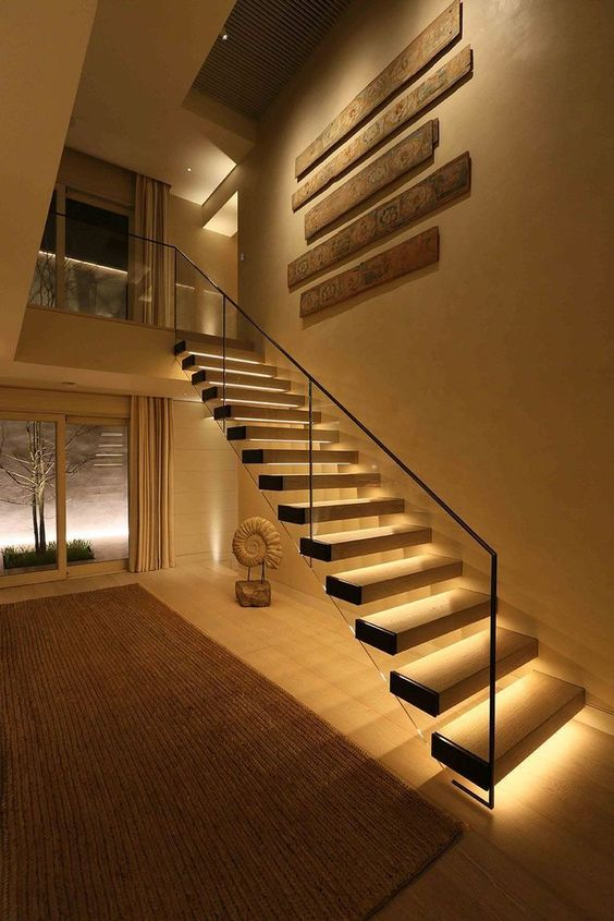 a floating staircase with additional lights built-in that make it stand out and look bolder and catchier