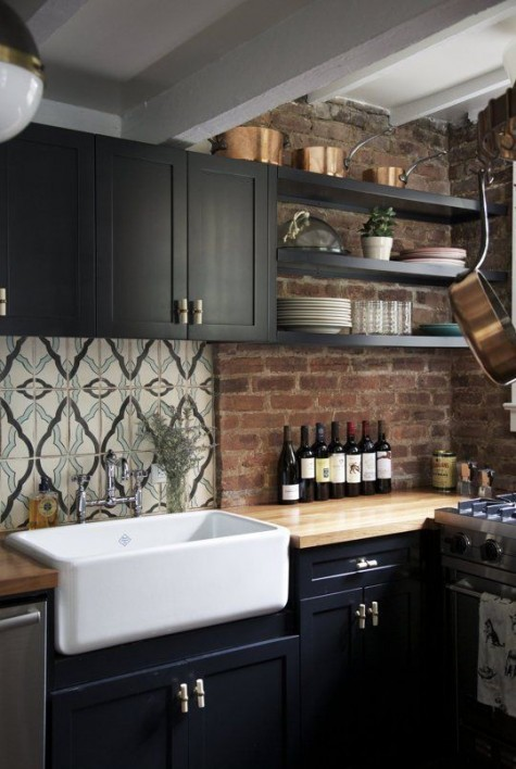 a moody kitchen with black cabients, light-colored butcherblock countertops with a red brick backsplash