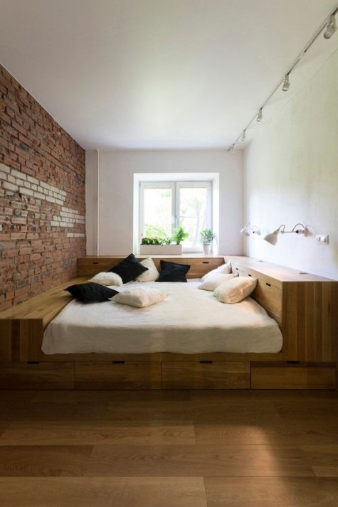 a small bedroom with a podium bed with much built in storage that allows to declutter the space