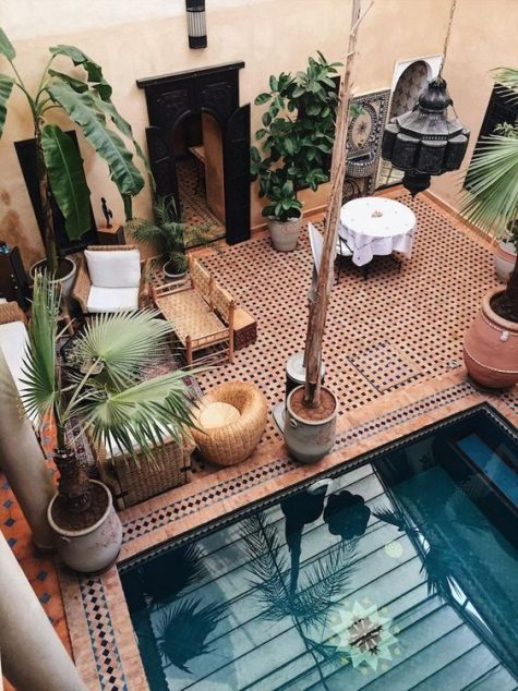 a warm colored Moroccan pool space done with wicker and leather furniture, potted plants, hanging lanterns and a pool with steps