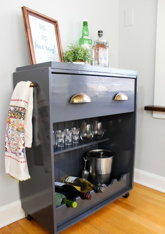 a graphite grey IKEA Rast hack into a half open home bar with gold pulls and an open compartment for glasses and bottles