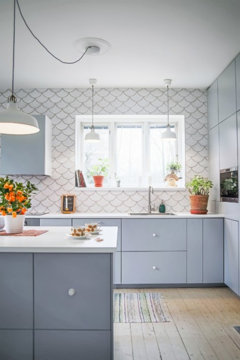 a matte grey kitchen with a white fishscale tile backsplash that is spread on the whole wall