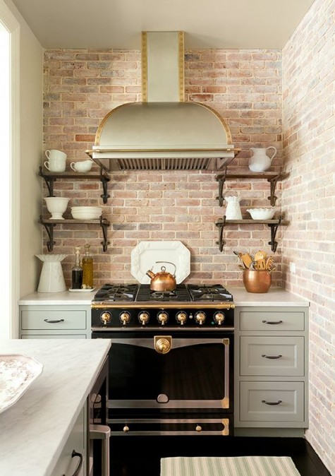 a small vintage-inspired kitchen with a red brick backsplash and a black retro cooker