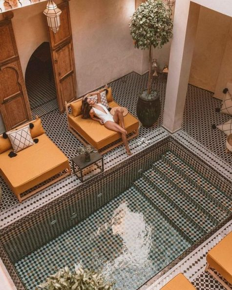 an amazing Moroccan pool space all clad with mosaic tiles, ocher daybeds, potted greenery and chic Moroccan lanterns
