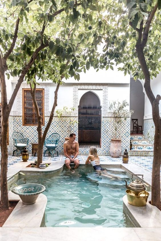 a Moroccan boho pool space fully clad with beautiful tiles and with potted greenery and trees growing around the pool