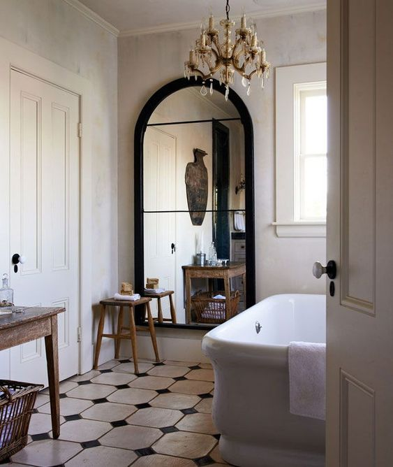 a chic vintage-inspired bathroom with a beautiful arched mirror in a black frame looks wow