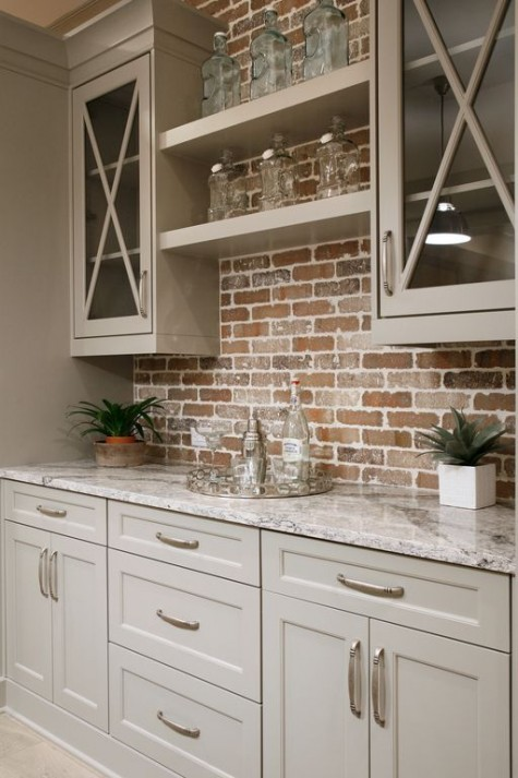 a small farmhouse kitchen with beige cabinets with a red brick backsplash and marble countertops