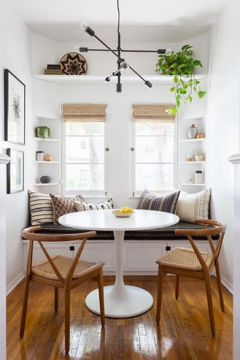 a tiny dining space with built-in shelves and a bench with storage drawers that solve the storage problem