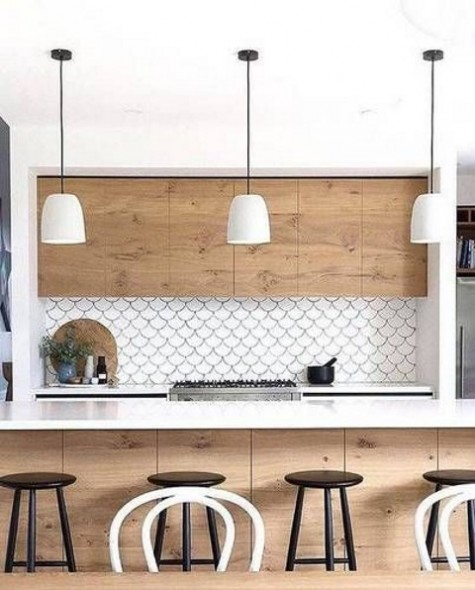 a white and light-colored kitchen is accentuated with a white fishscale tile backsplash