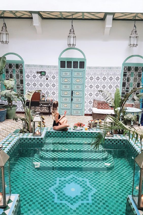 a bold Moroccan riad with a mosaic tile pool, potted plants and growing ones and some candle lanterns