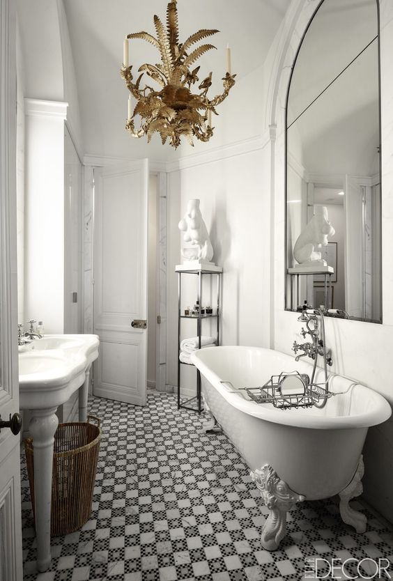 a refined monochromatic bathroom with an oversized arched mirror and a beautiful gold chandelier for a chic touch