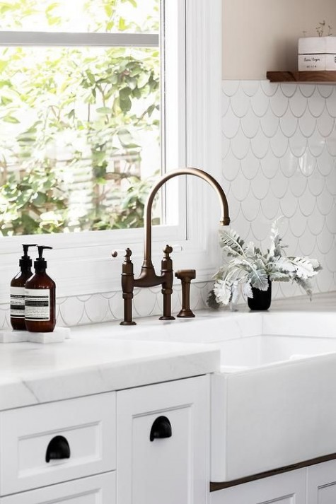 a white kitchen with black accents is made more eye-catching with a cool white fishscale tile backsplash highlighted with black grout