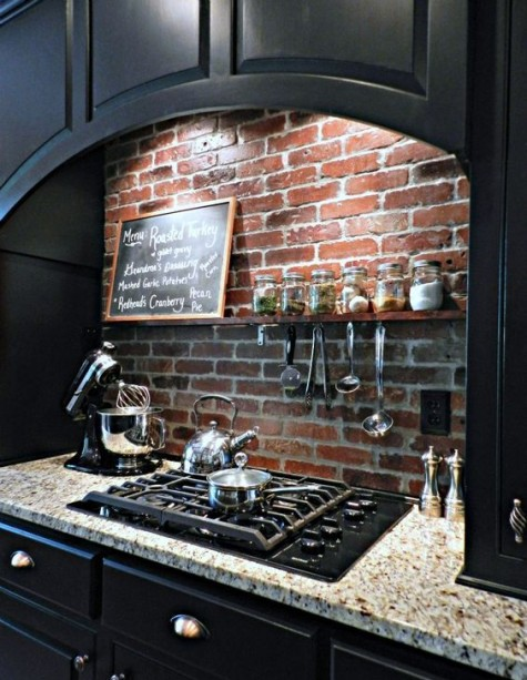 black cabinets and a red brick backsplash and a stone countertop look bold, bright and very eye-catching