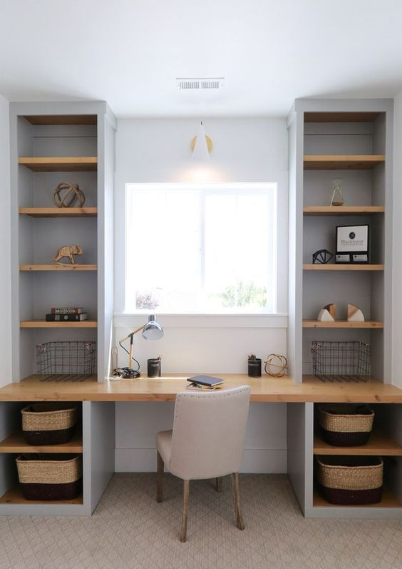 a small home office with a fully built in unit   a desk and open shelves to maximize functionality