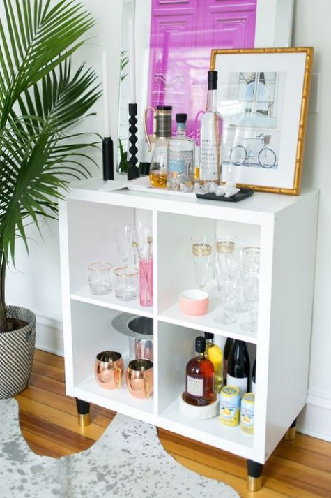 a stylish home bar made of an IKEA Kallax shelf with elegant gilded legs will fit many modern spaces