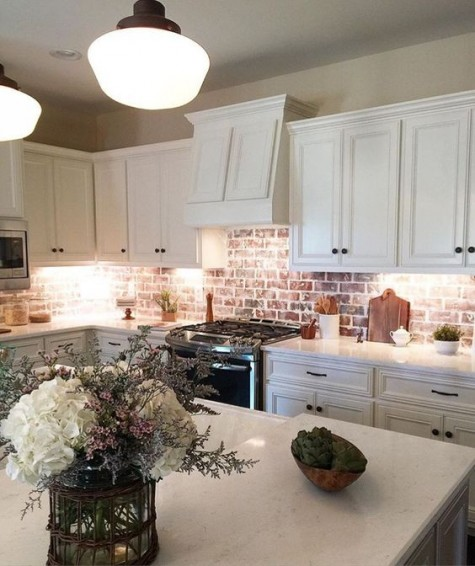 creamy traditional cabinets look cool with a red brick backsplash that brings color and texture in