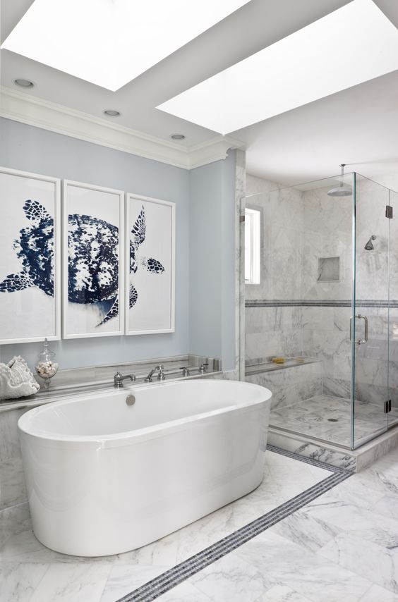 a coastal bathroom with a beautiful triop of artworks showing off a turtle and large seashells to make it feel like sea