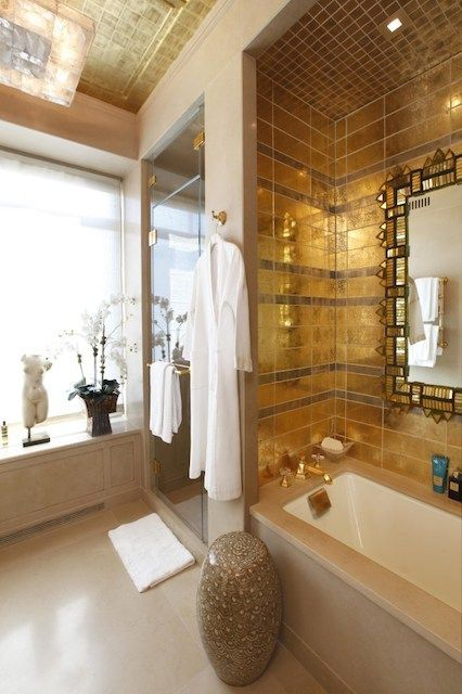 gorgeous gold tiles around the bathtub to mark this space and give a slight Moroccan luxury touch to the zone